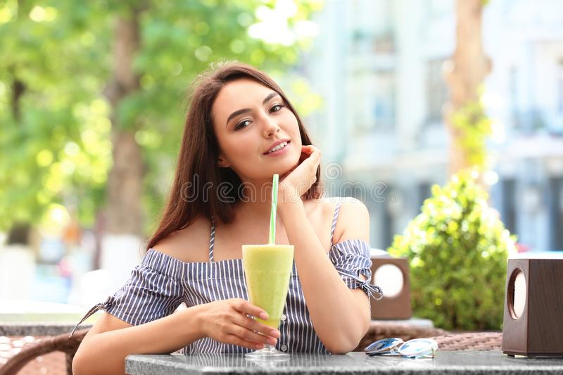 Pretty young woman drinking smoothie stock photo