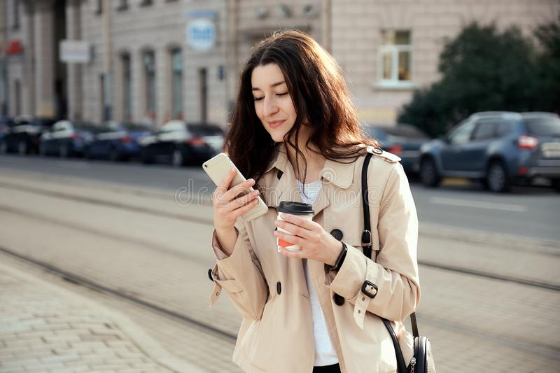 Pretty young woman drinking takeout coffee cup outdoors, talking on the phone, royalty free stock photo