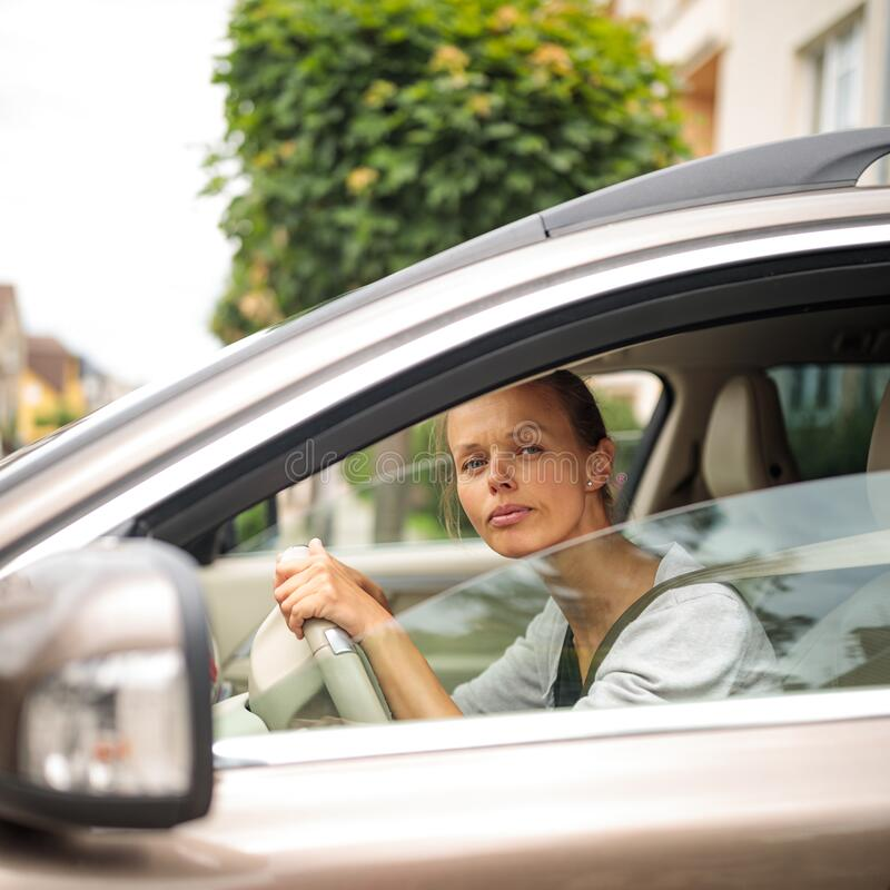 Pretty, young woman  driving a car royalty free stock photography