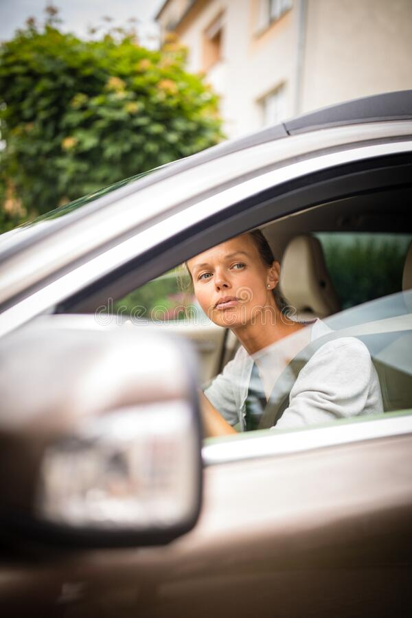 Pretty, young woman  driving a car royalty free stock image