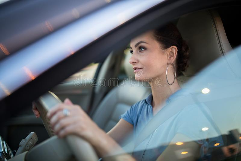 Pretty, young woman  driving a car stock images