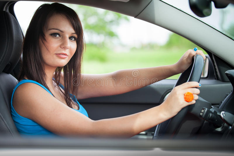 Pretty young woman driving her car royalty free stock photos
