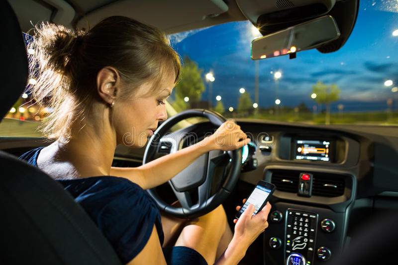 pretty, young woman driving her modern car at night, in a city stock photos