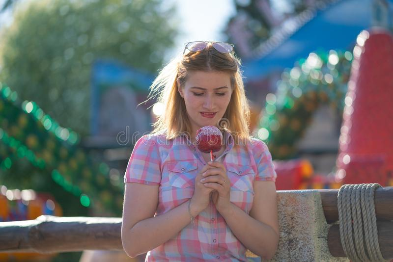 Pretty young woman eating and biting red caramel apple in the park in the sunny day. Alone smile happy stock images