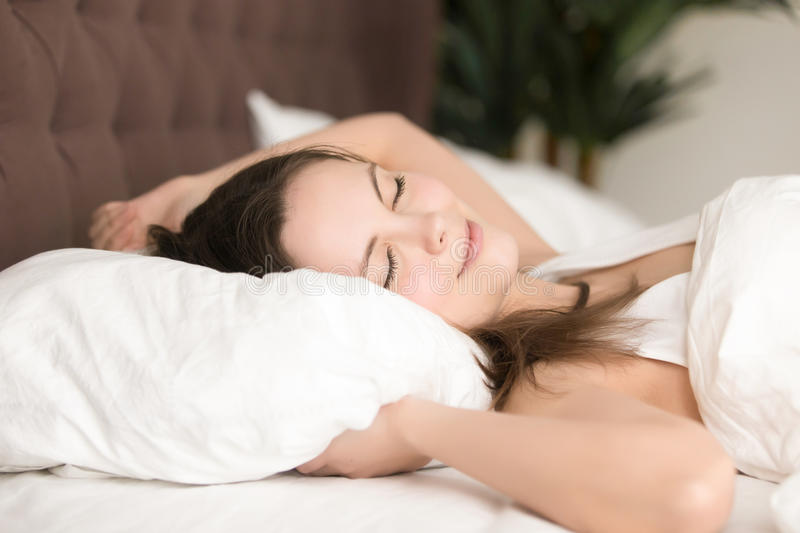Pretty young woman enjoys long sleep in bed. Pretty young woman enjoys long sleep on her weekend at home. Cute lady lying relaxed with closed eyes, luxuriates in stock photo