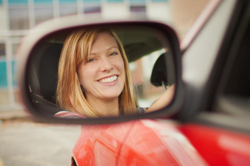 Woman in car mirror. Pretty young woman face in car mirror stock photography