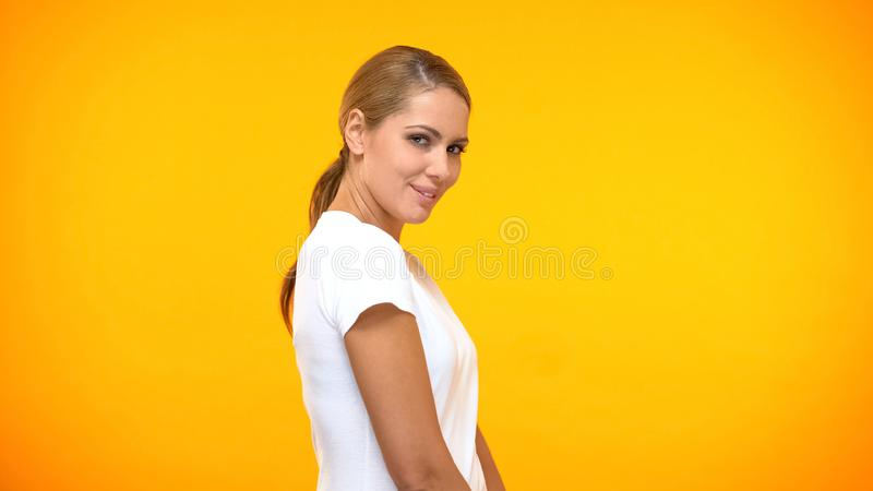 Pretty young woman flirting on camera orange background, female confidence royalty free stock image