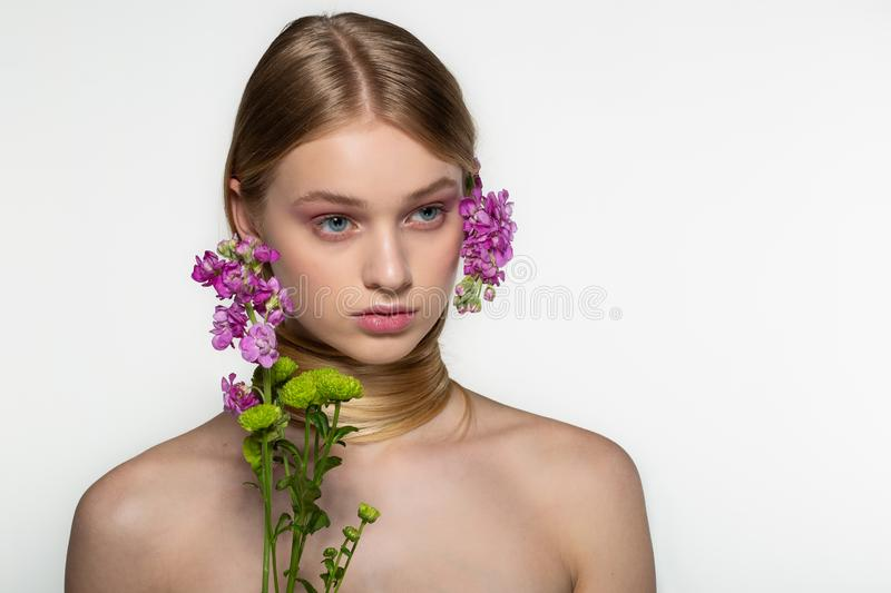 Pretty young woman with fresh spring look, wonderful hair, nice makeup, flowers near her face and in hair. Beauty and royalty free stock photos