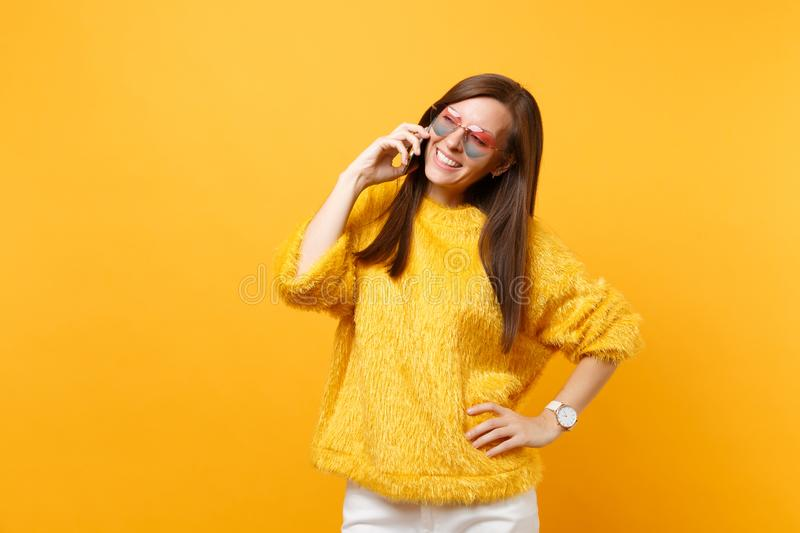 Pretty young woman in fur sweater, heart glasses talking on mobile phone, conducting pleasant conversation isolated on stock images