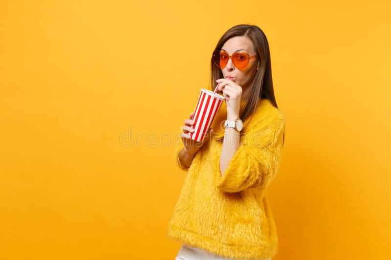 Pretty young woman in fur sweater and heart orange glasses drinking cola or soda from plastic cup isolated on bright. Yellow background. People sincere emotions stock photography