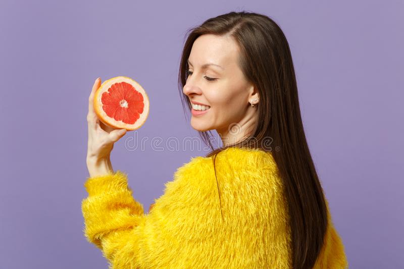 Pretty young woman in fur sweater holding in hand half of fresh ripe grapefruit  on violet pastel wall. Background in studio. People vivid lifestyle, relax stock photography