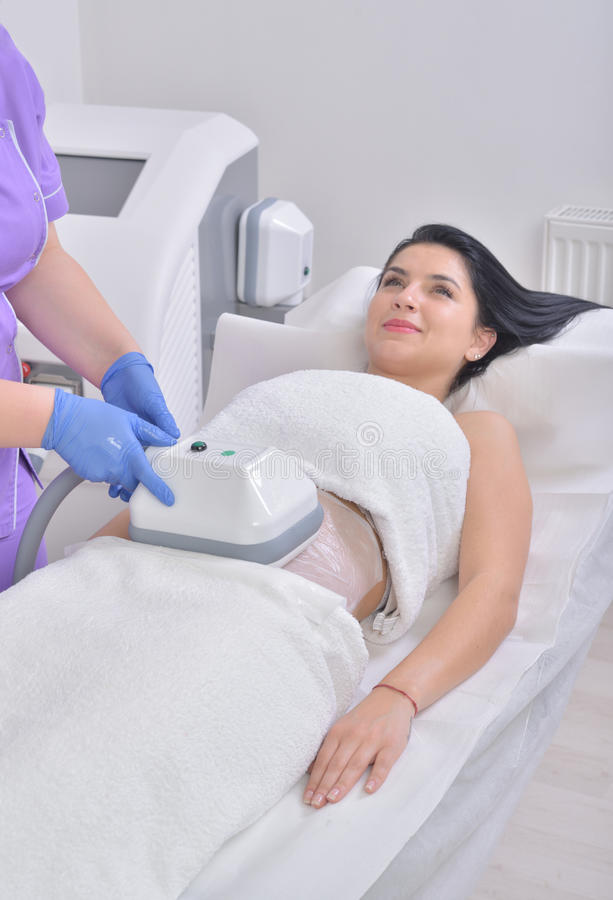 Pretty young woman getting cryolipolyse fat treatment in profess royalty free stock photography