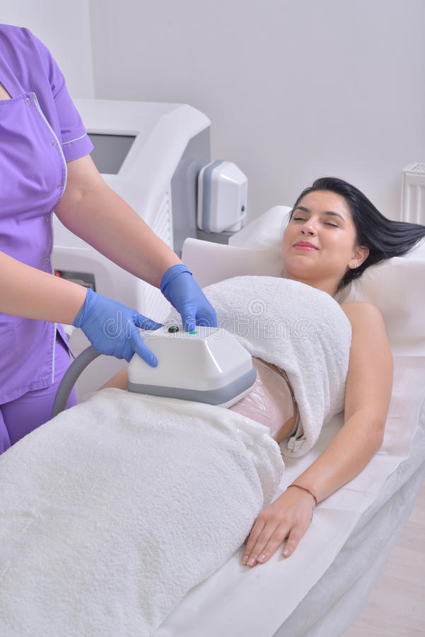 Pretty young woman getting cryolipolyse fat treatment in profess. Ional cosmetic cabinet stock photo