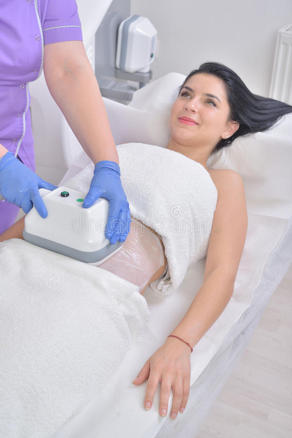 Pretty young woman getting cryolipolyse fat treatment in profess royalty free stock photos