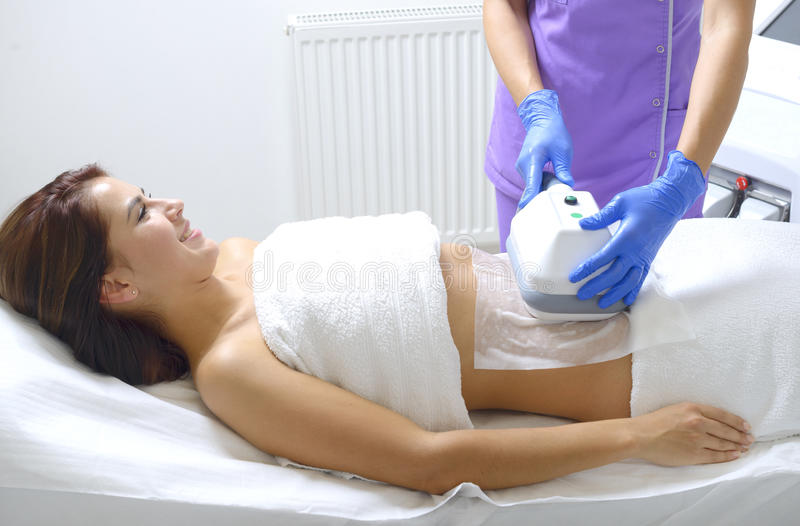 Pretty young woman getting cryolipolyse treatment in cabinet royalty free stock image