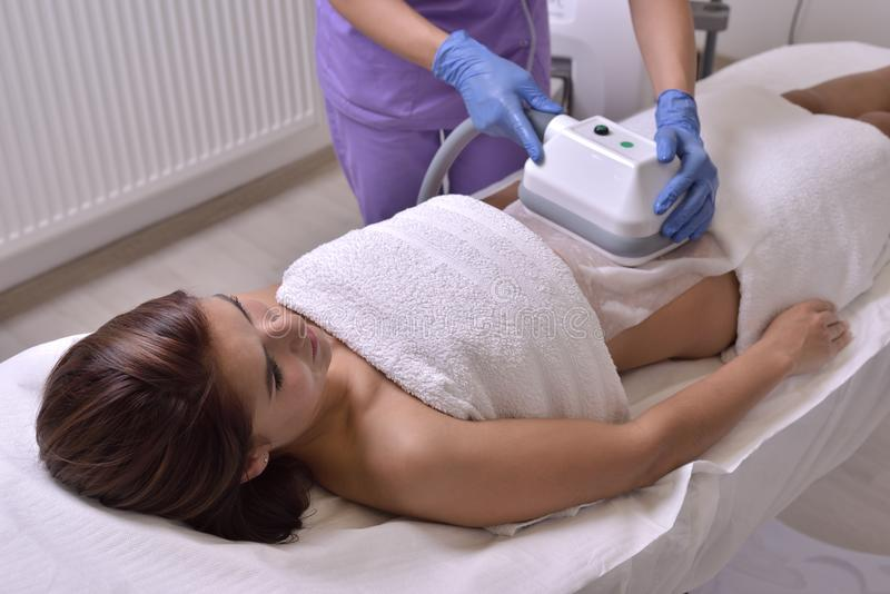 Pretty young woman getting cryolipolyse treatment in cosmetic ca. Binet royalty free stock images