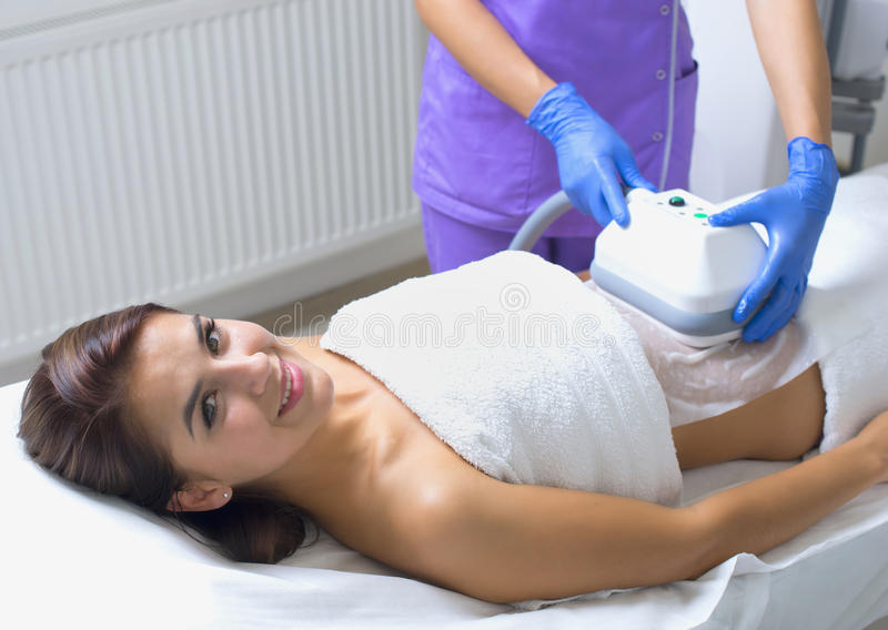 Pretty young woman getting cryolipolyse treatment. In cosmetic cabinet stock images