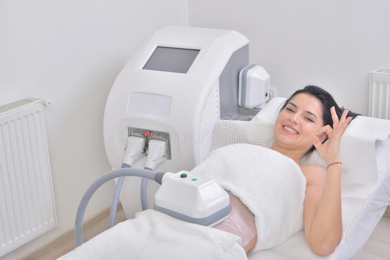 Pretty young woman getting cryolipolyse treatment in professional cosmetic cabinet royalty free stock images