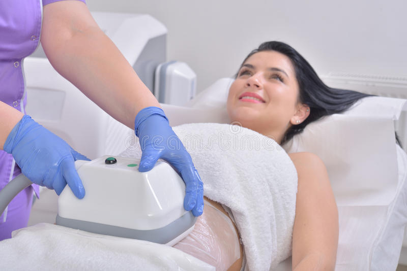 Pretty young woman getting cryolipolyse treatment in professional cosmetic cabinet royalty free stock photography