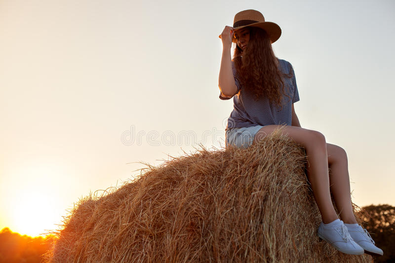 Pretty young woman in hat sitting on a hay bale. Pretty young woman with long hair in hat wearing shorts, t-shirt and white sneakers sitting on a hay bale in royalty free stock image