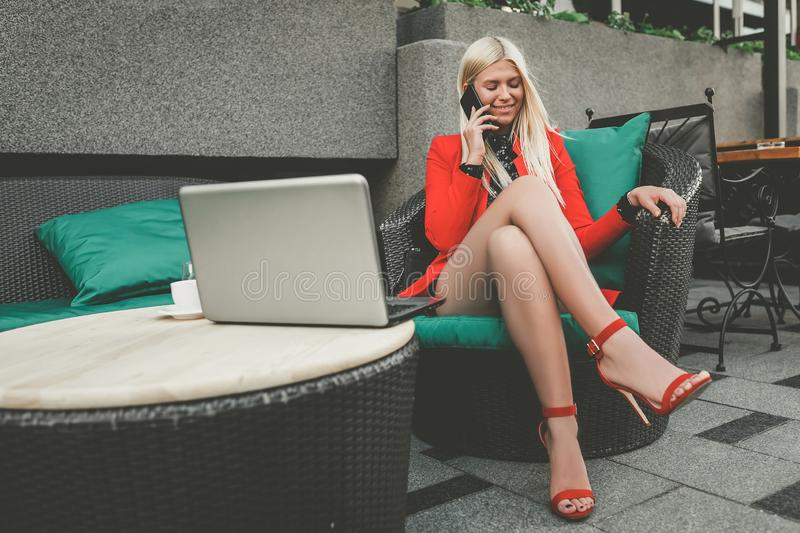 Pretty young woman having cell phone conversation while sitting front open laptop computer stock image