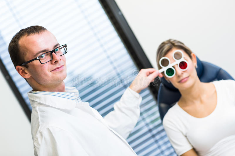 Pretty young woman having her eyes examined. Optometry concept - pretty young women having her eyes examined by an eye doctor royalty free stock photo