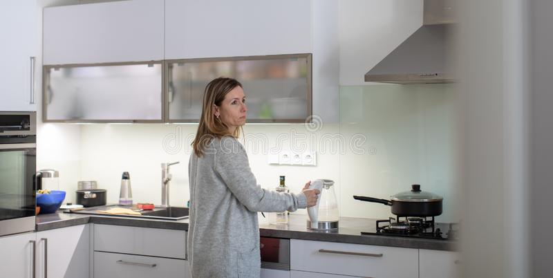 Pretty, young woman in her modern bright kitchen royalty free stock images