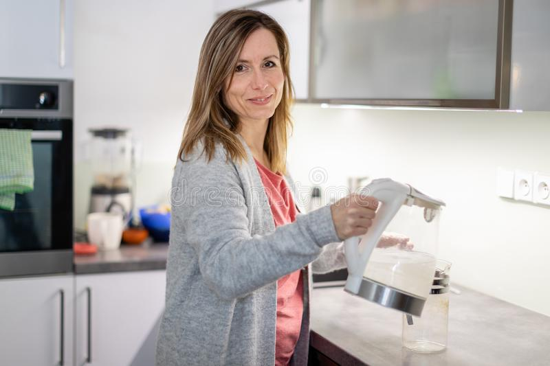 Pretty, young woman in her modern bright kitchen stock photography