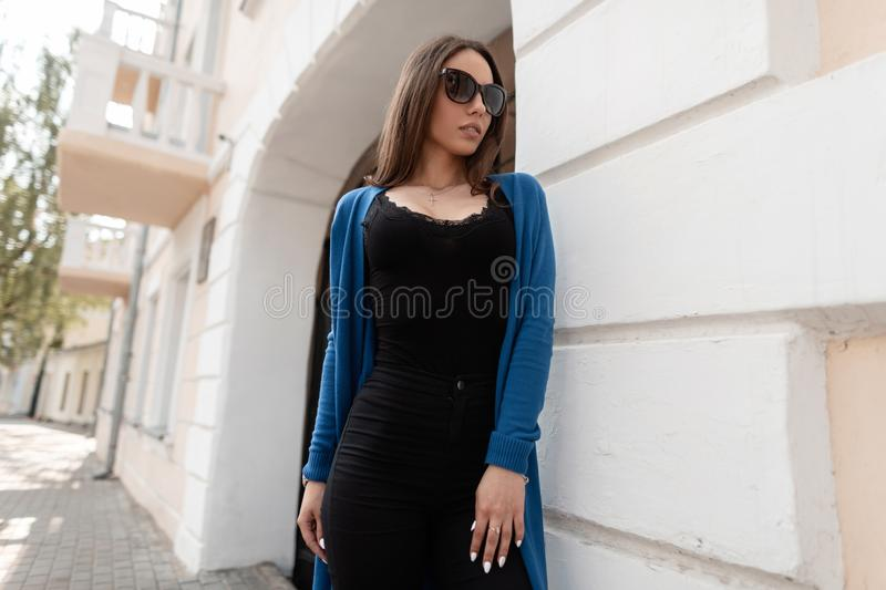 Pretty young woman hipster in stylish black top in a knitted cape in trendy jeans in dark sunglasses is posing. Near a modern building in the city. Attractive royalty free stock images