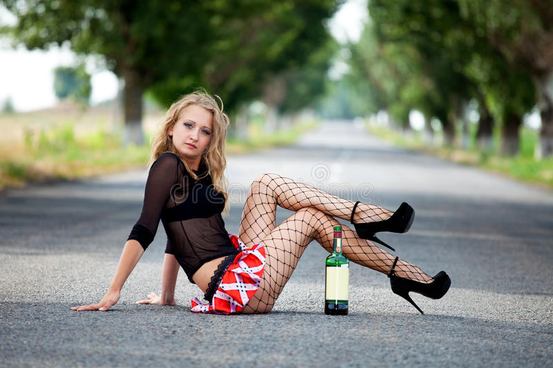Pretty young woman hitchhiking. Along a road royalty free stock photos