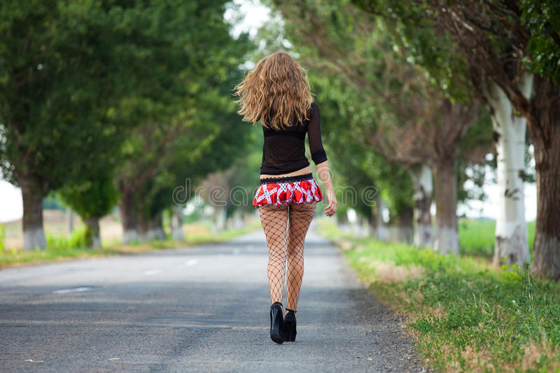Pretty young woman hitchhiking. Along a road stock photo