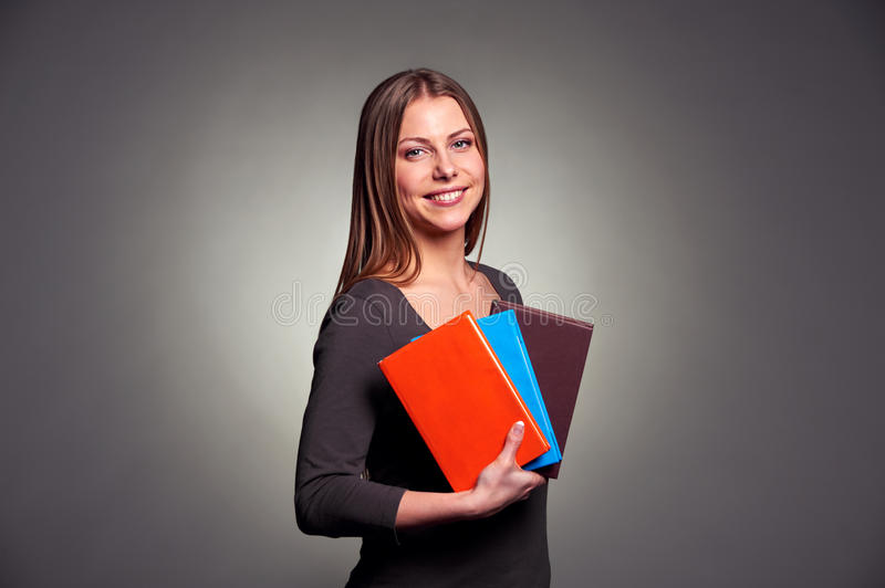 Pretty young woman holding the books