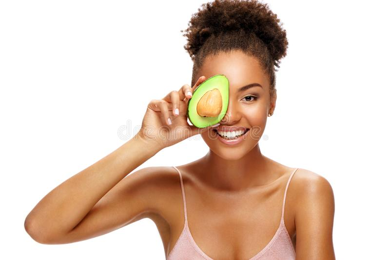 Pretty young woman holding half an avocado in front of her face. Photo of smiling african woman isolated on white background. Beauty & Skin care concept royalty free stock photos