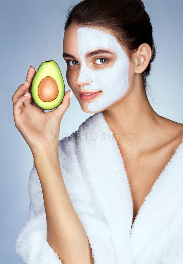 Pretty young woman holding half an avocado in hand. stock images