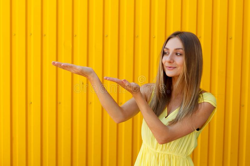 Pretty young woman holding hands above presenting your product w royalty free stock image
