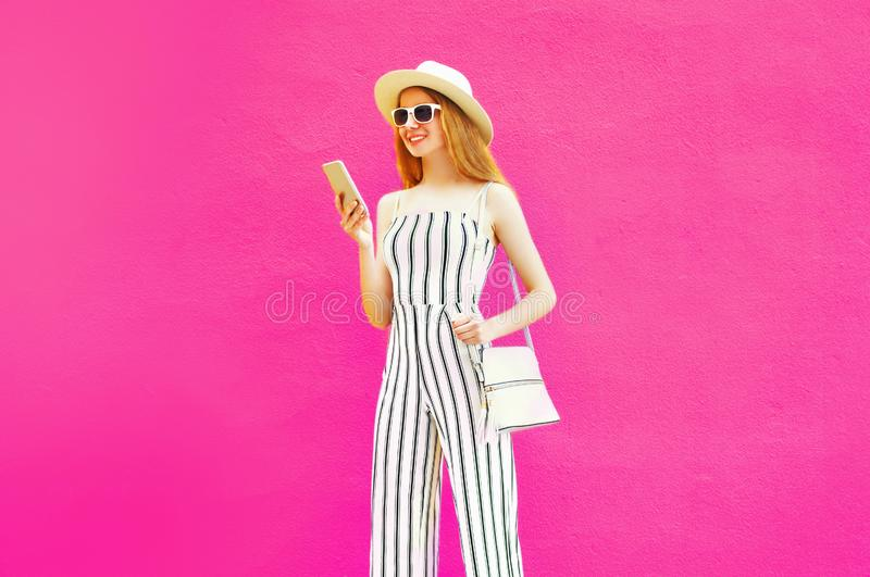 pretty young woman holding smartphone in summer round hat, white striped jumsuit on colorful pink wall stock images