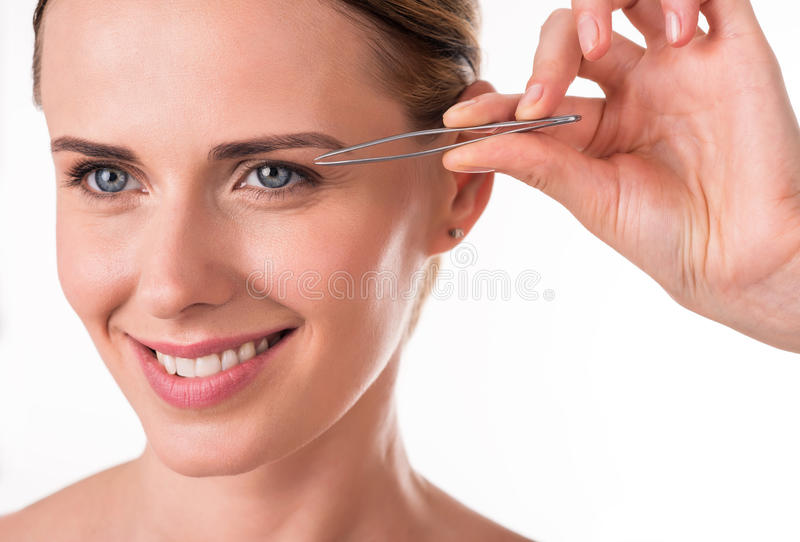 Pretty young woman holding tweezers. Every detail. Close-up studio portrait of smiling and positive young woman using tweezers by pinching her perfect eyebrows royalty free stock image