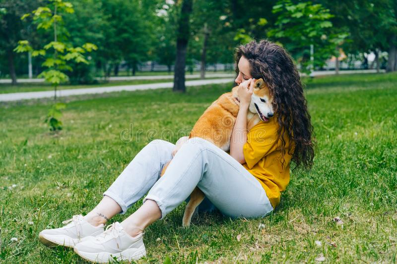 Pretty young woman hugging shiba inu dog and smiling sitting on grass in park royalty free stock photos