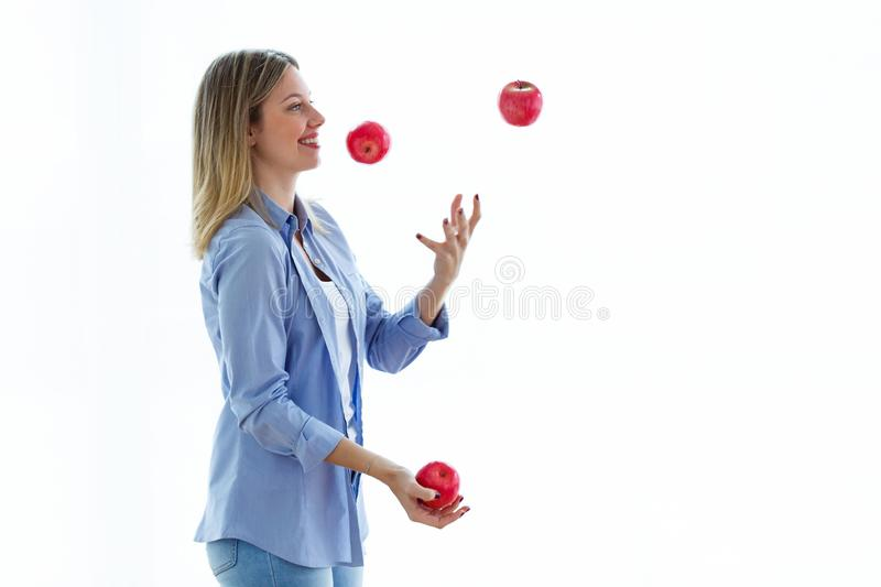 Pretty young woman juggling with red apples over white background. Shot of pretty young woman juggling with red apples over white background stock image
