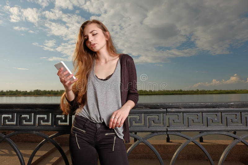 Pretty Young Woman Leaning Back Against Railings on Embankment While Using her Smartphone Reading Sms. Instagram effect, a lot of space for text on sky stock images