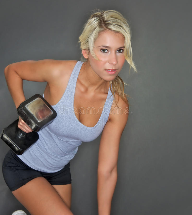 Pretty young woman lifting weights. Photo of pretty young blond woman lifting weights royalty free stock photography