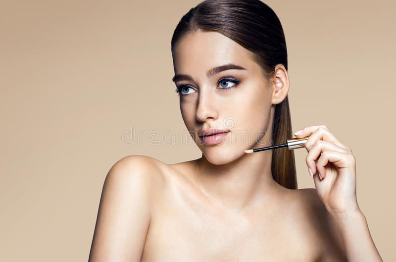 Pretty young woman with lip gloss stock image