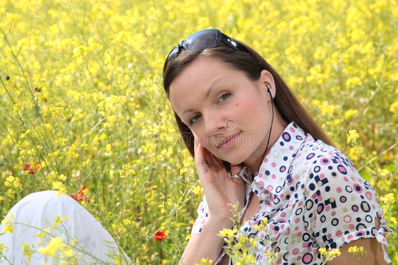 Pretty young woman listening to. Pretty young woman wearing earphones listening to music on a meadow royalty free stock photos