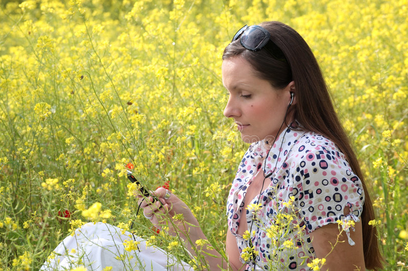 Pretty young woman listening to. Pretty young woman wearing earphones listening to music, holding a mobile phone on a meadow royalty free stock photo