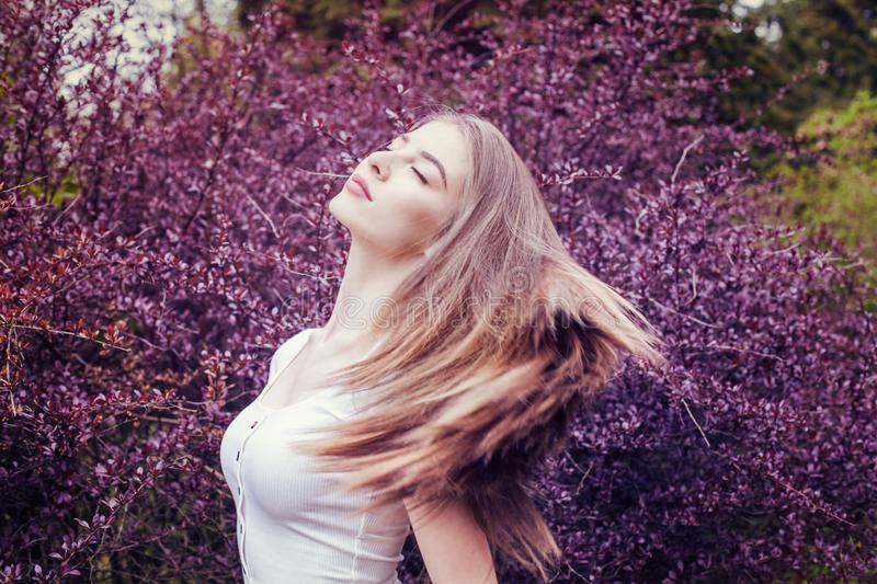 Pretty young woman with long straight hair portrait against purple flowers background royalty free stock photos