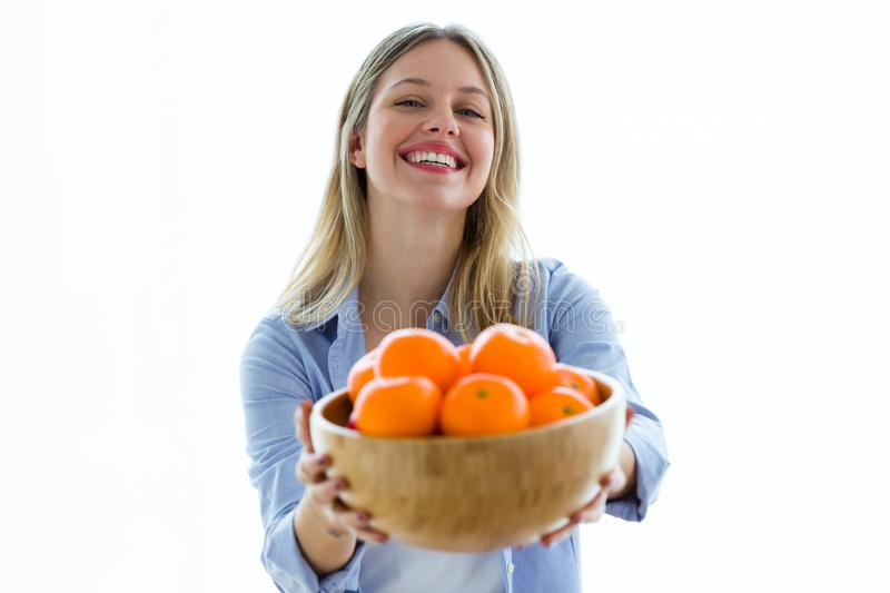 Pretty young woman looking at camera while holding a bowl with oranges over white background. Portrait of pretty young woman looking at camera while holding a royalty free stock photography