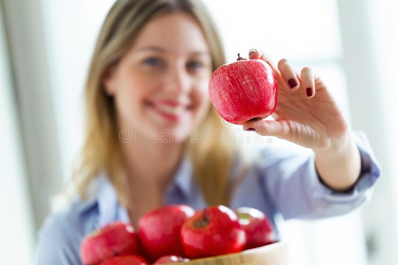 Pretty young woman looking at camera while showing red apple at home. Portrait of pretty young woman looking at camera while showing red apple at home royalty free stock image