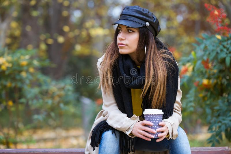 Pretty young woman looking sideways while sitting in a bench on the park in autumn royalty free stock photos