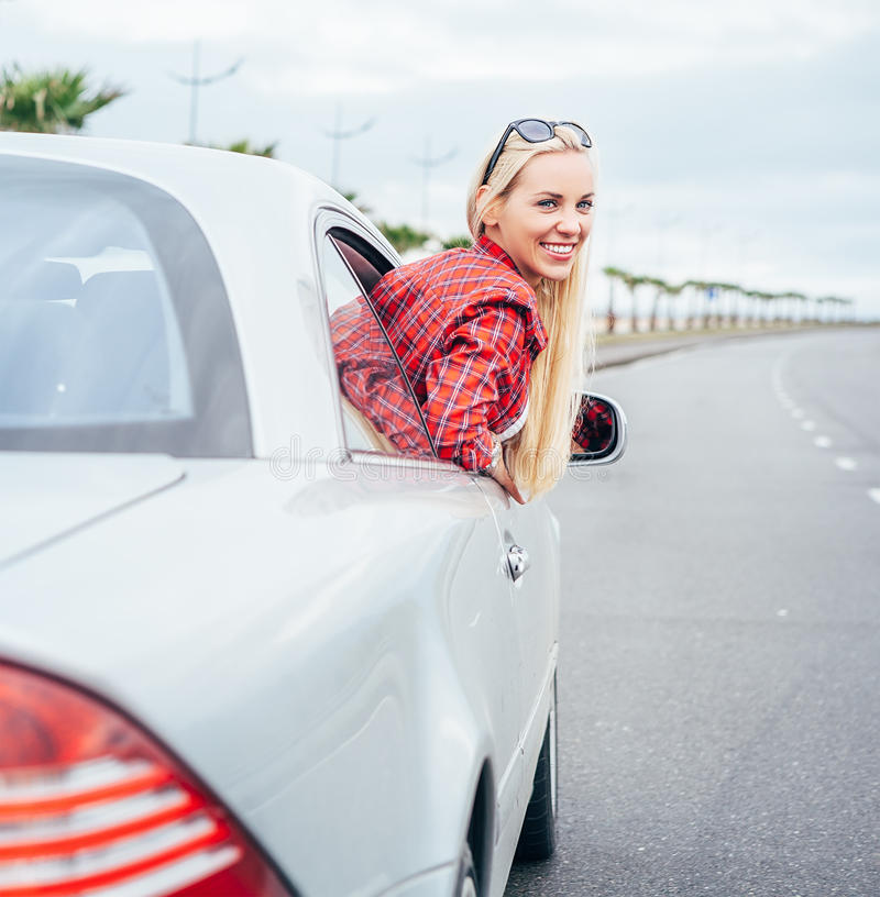 Pretty young woman looks out from car stock photography