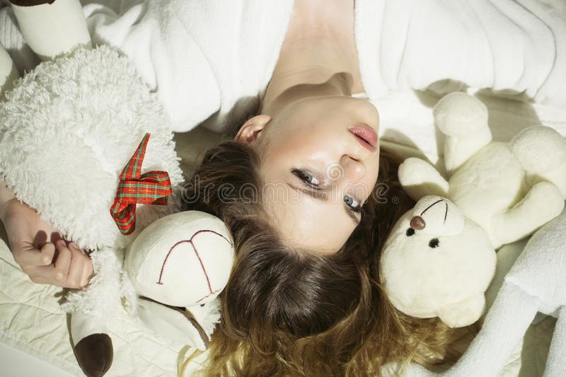 Pretty young woman lying on the floor with a teddy bear royalty free stock photo